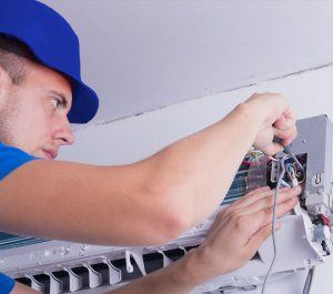 Air Conditioner Technician repairing AC unit in Austin TX